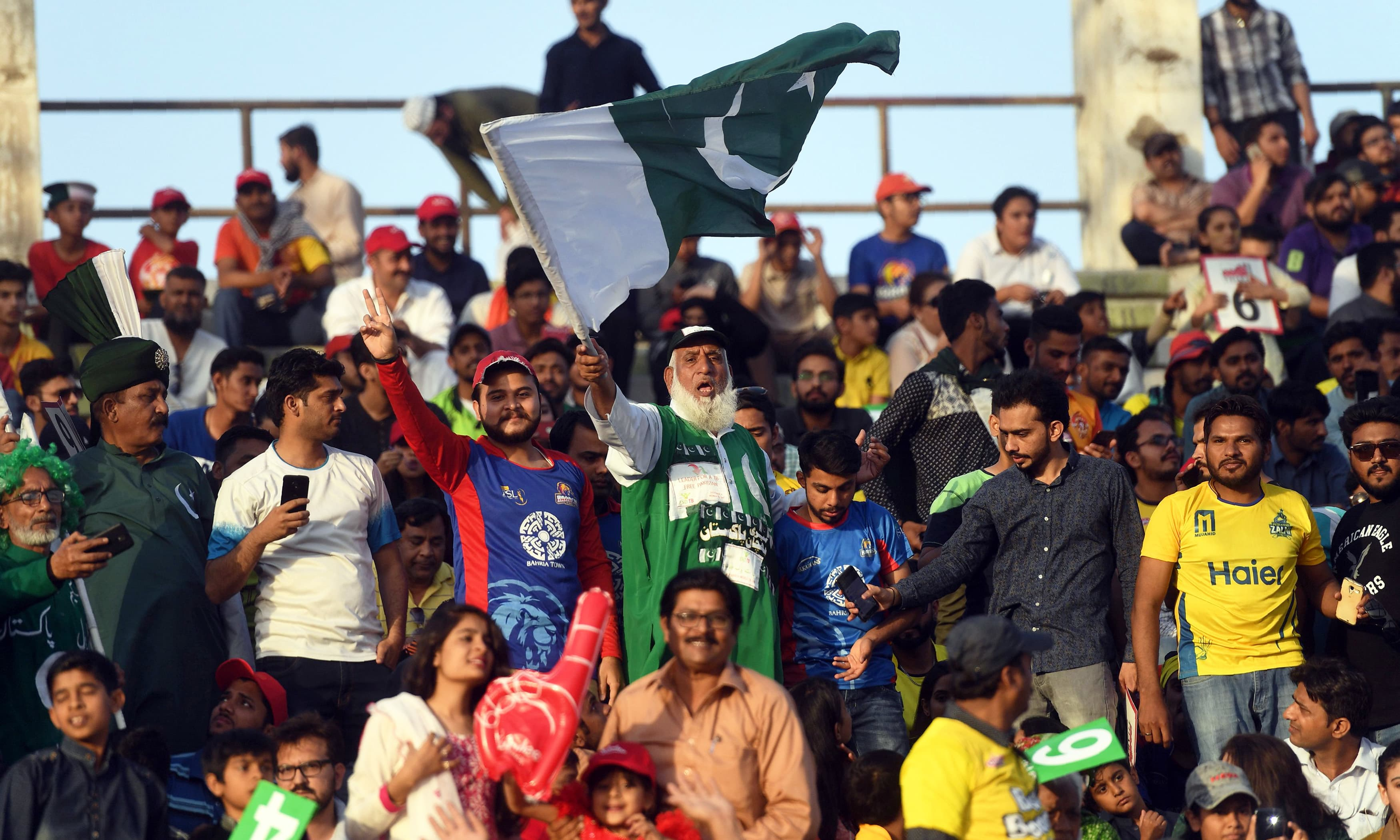 Cricket fans wave the national flag during PSL final match between Peshawar Zalmi and Islamabad United. —AFP