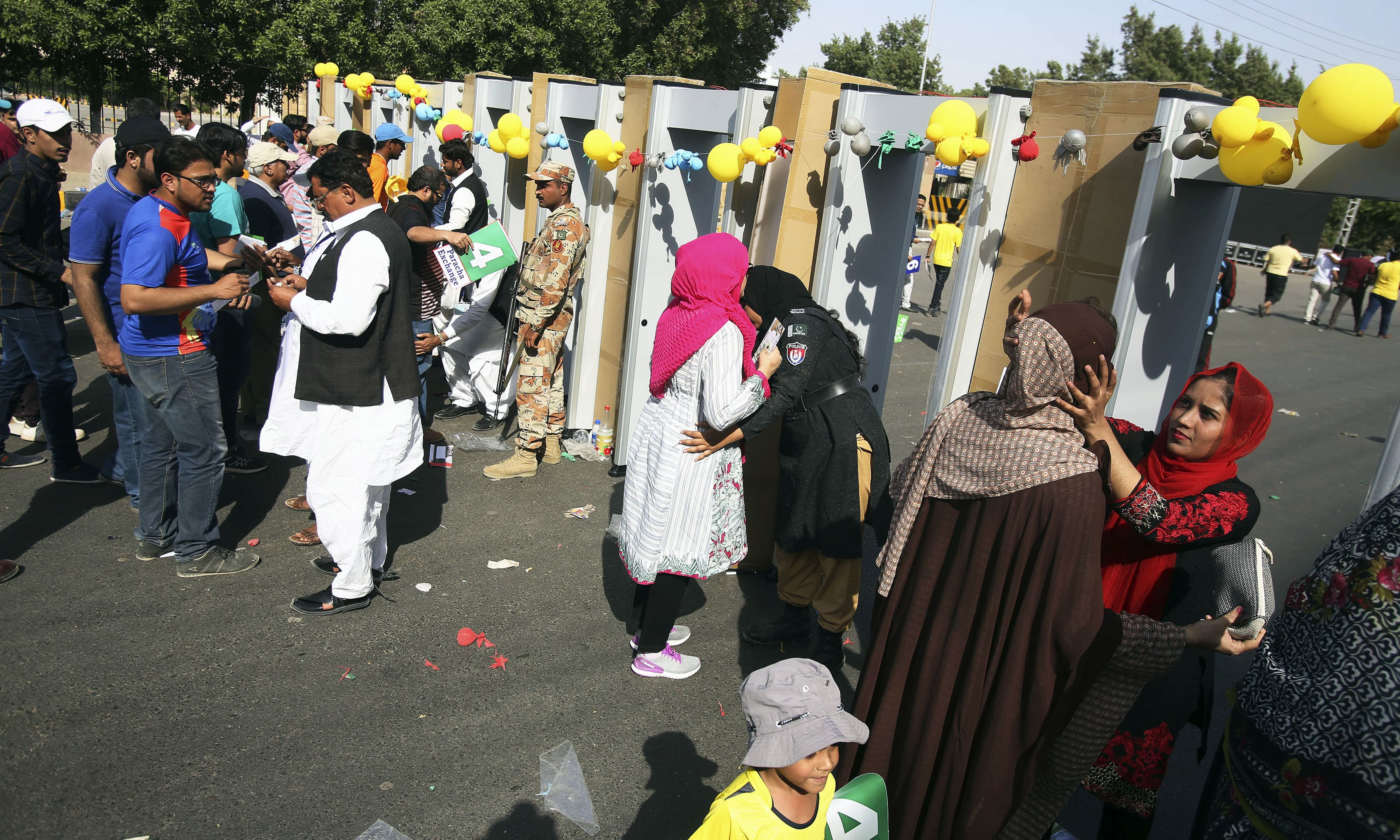 Security officials frisk cricket fans outside the National stadium in Karachi. —AP