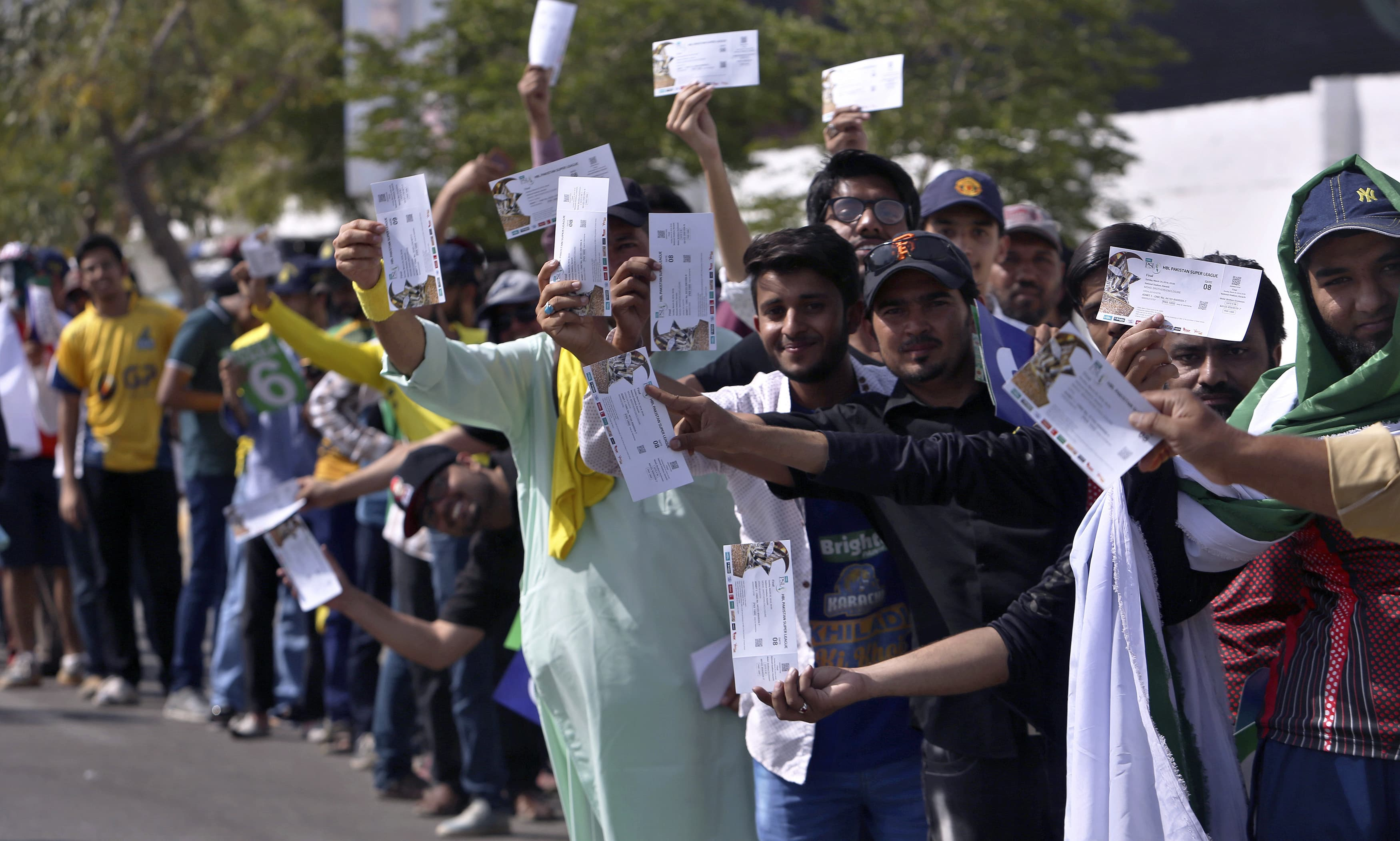 Cricket fans display their tickets as they stand in a queue to enter the stadium. —AP