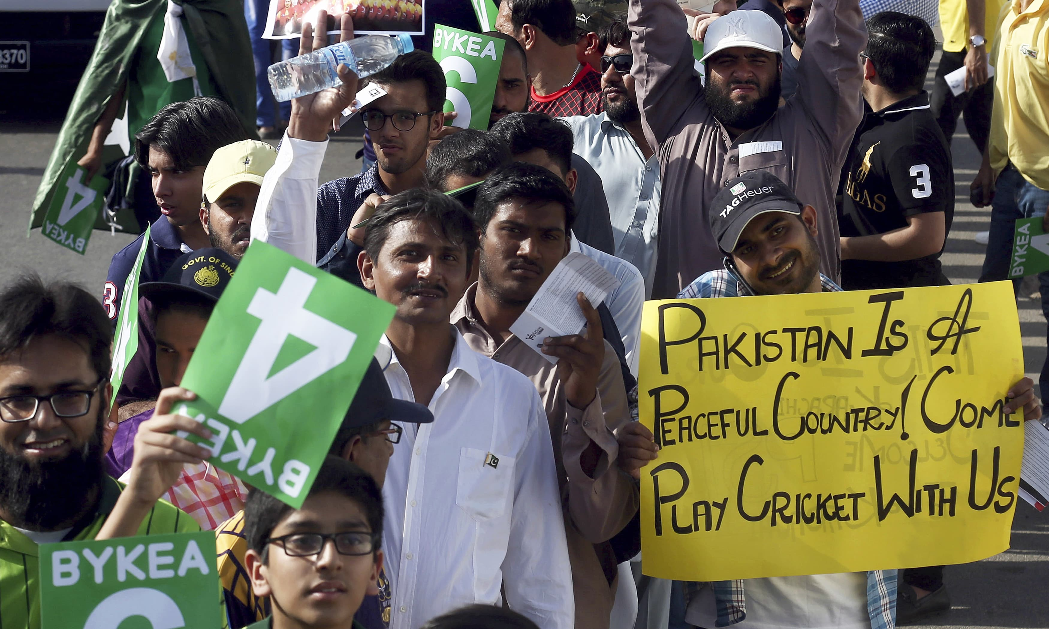 A cricket fan displays a placard while standing in a long queue to enter the National stadium. —AP
