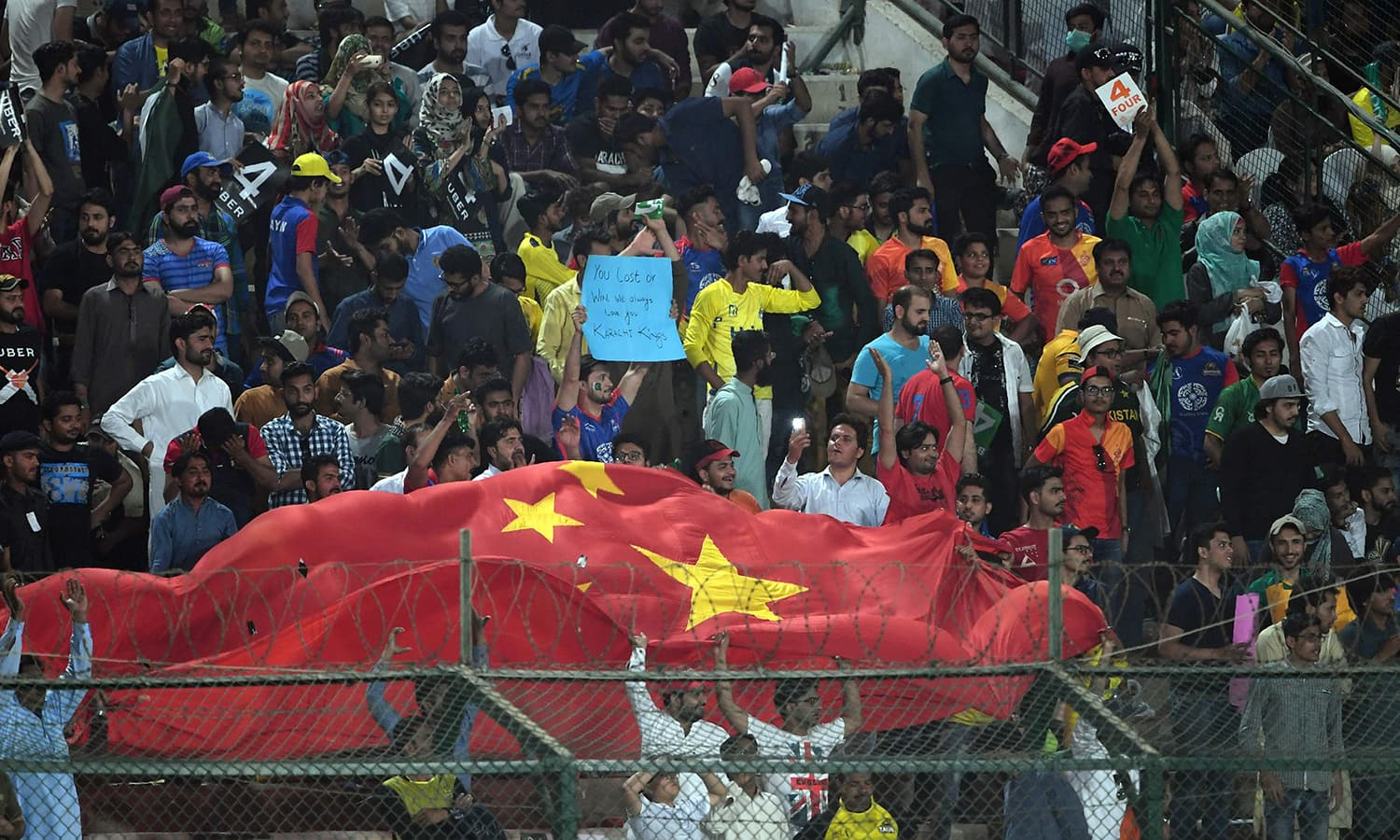 Cricket fans waves Chinese flag during the PSL final match at the National Cricket Stadium. —AFP