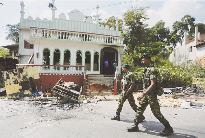 SRI LANKA'S Special Task Force soldiers walk past a damaged mosque after a clash between two communities in Digana, central district of Kandy, in this file picture taken on March 8.—Reuters