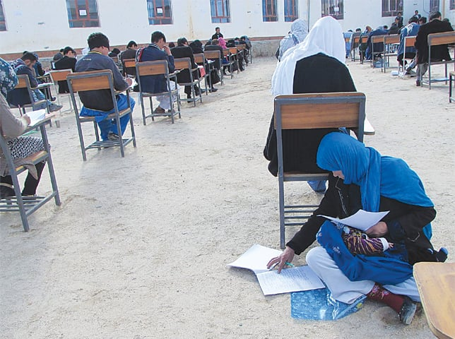 AFGHAN student Jahantab Ahmadi, 25, sitting on the ground as her baby lies on her lap as she takes an entrance exam for Nasir Khusraw private university, in the central city of Nili, the provincial capital of Daykundi province. The March 16 picture was obtained from the Facebook account of Afghan professor Yahya Erfan.—AFP