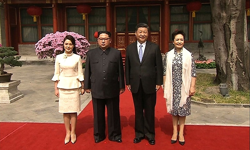 This video grab taken from footage released by China Central Television (CCTV) on March 28 shows Chinese President Xi Jinping (2nd R), his wife Peng Liyuan (R), North Korean leader Kim Jong Un (2nd-L) and his wife Ri Sol Ju (L) posing during their visit to Beijing this week. — AFP