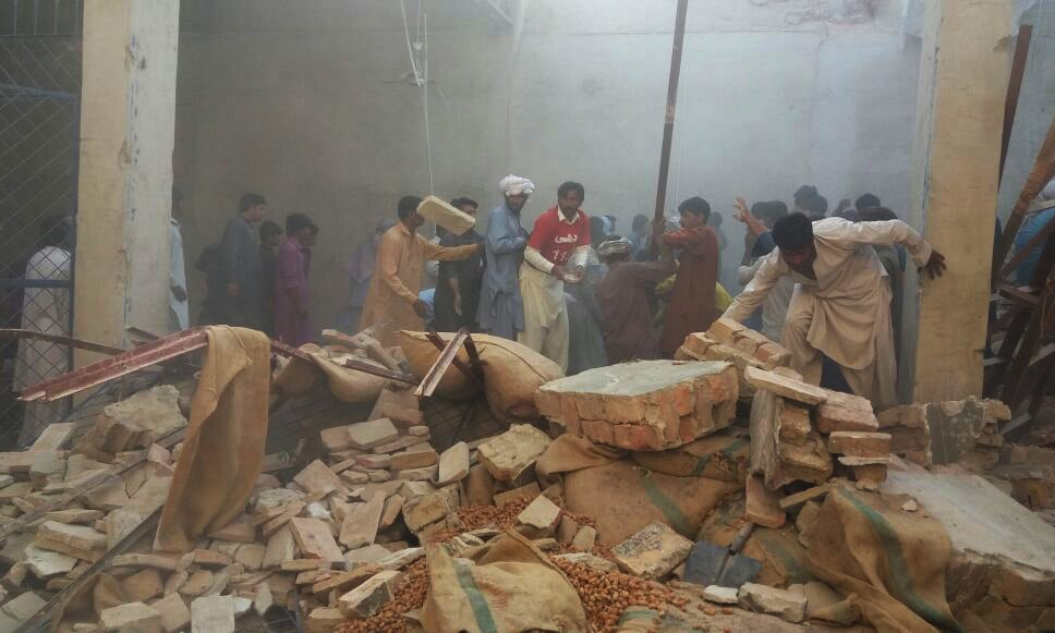 Labourers and rescue workers busy in rescue efforts at warehouse in Rohri's dates market. — photo by author