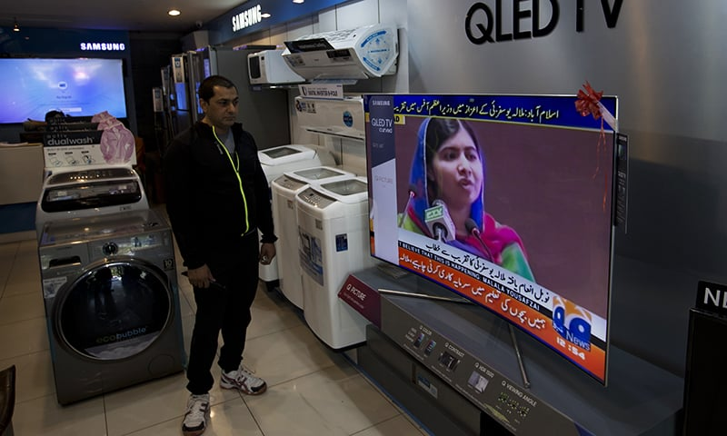 A shopkeeper listens to Malala Yousafzai addressing a reception at Prime Minister House in Islamabad. ─ AP