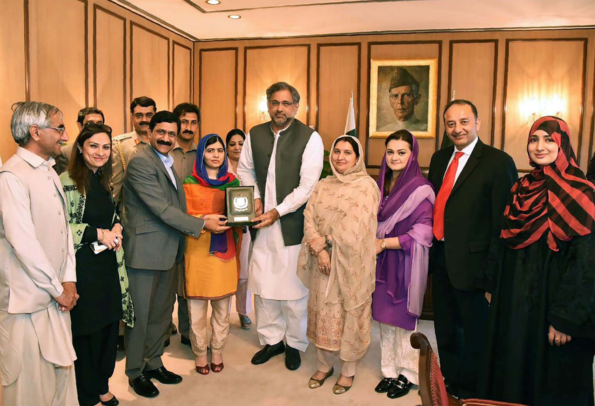 This handout photograph released by the Press Information Department (PID) on March 29, 2018, shows PM Abbasi (C) presenting a shield to Malala at Prime Minister Office during her visit to Islamabad. ─ AFP