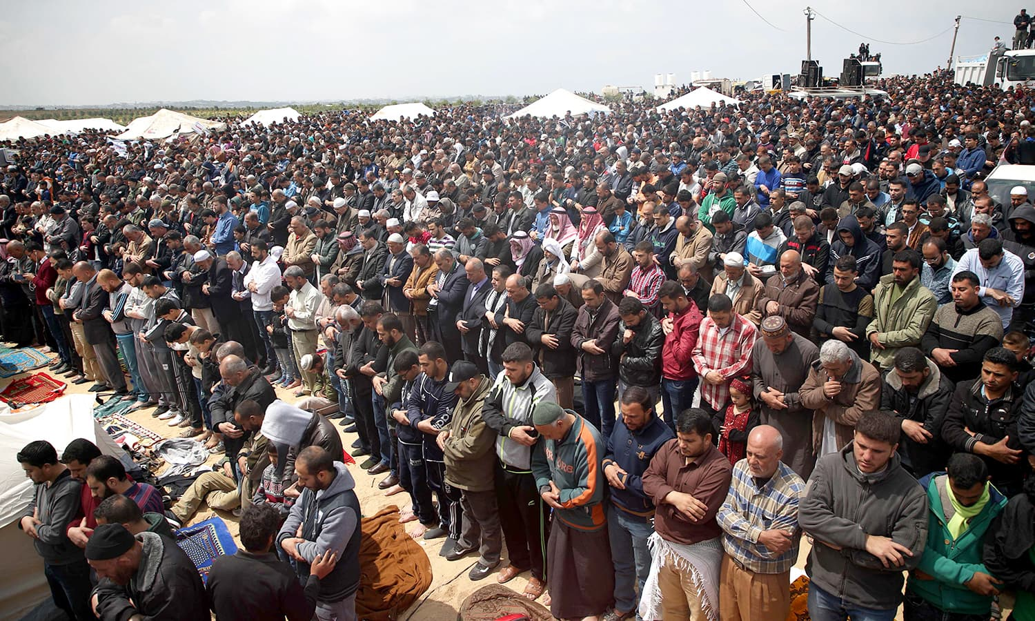 Worshippers perform Friday prayers during a tent city protest near the border with Israel. ─AFP
