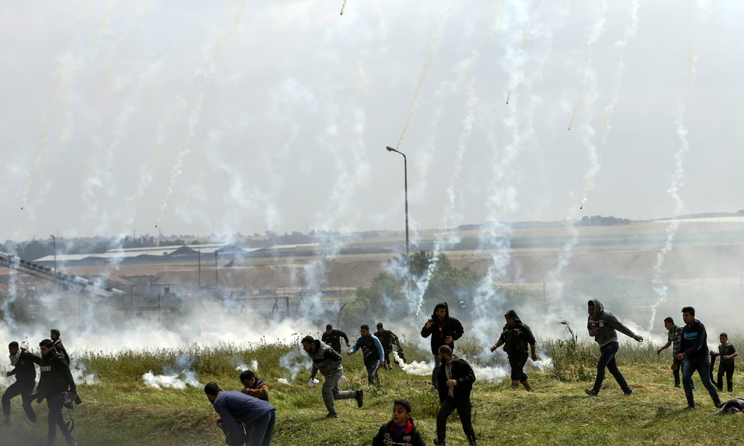 Palestinians fleeing as tear gas grenades begin to drop during a demonstration near the border with Israel east of Gaza City. ─AFP