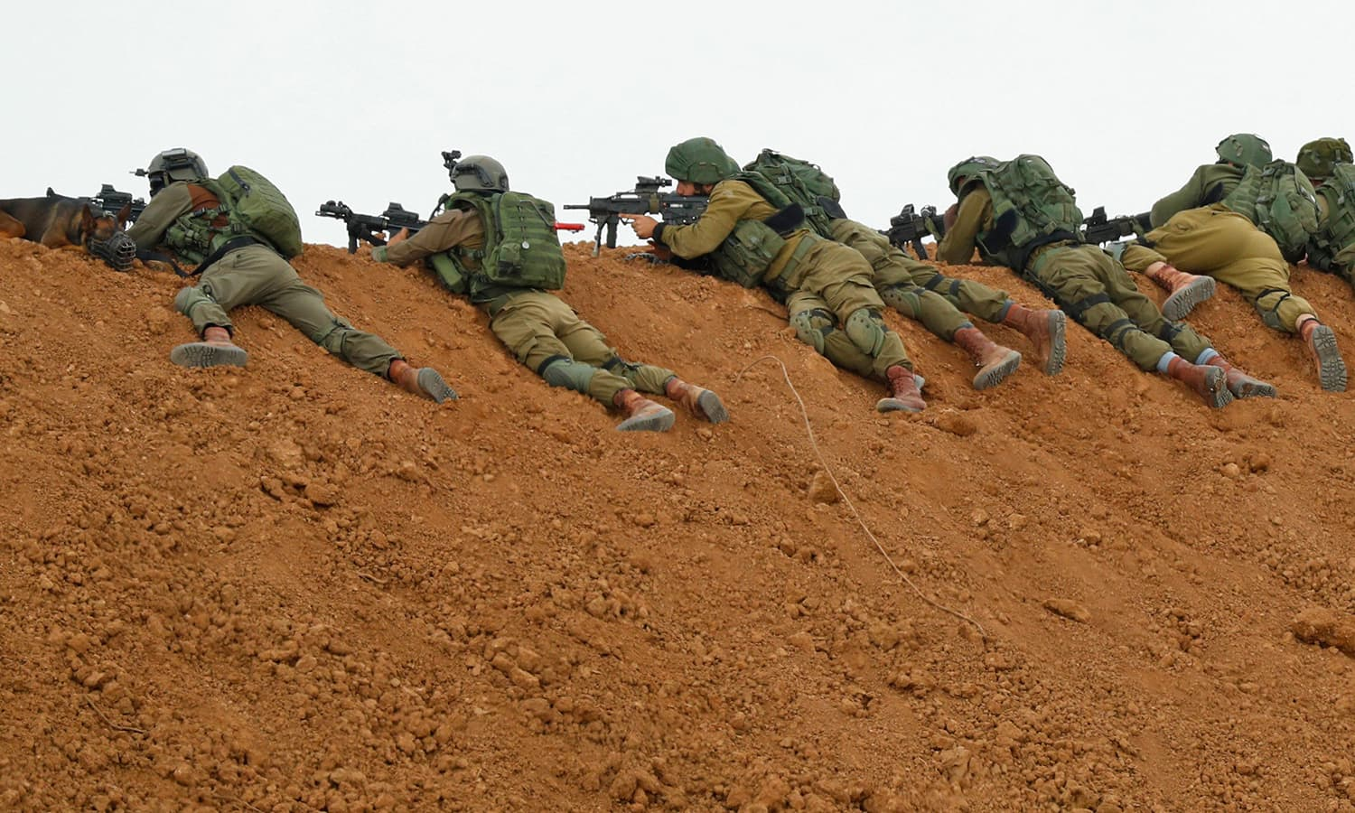 Israeli soldiers take aim as they lie prone over an earth barrier along the border with the Gaza Strip as Palestinians demonstrate on the other side. ─AFP