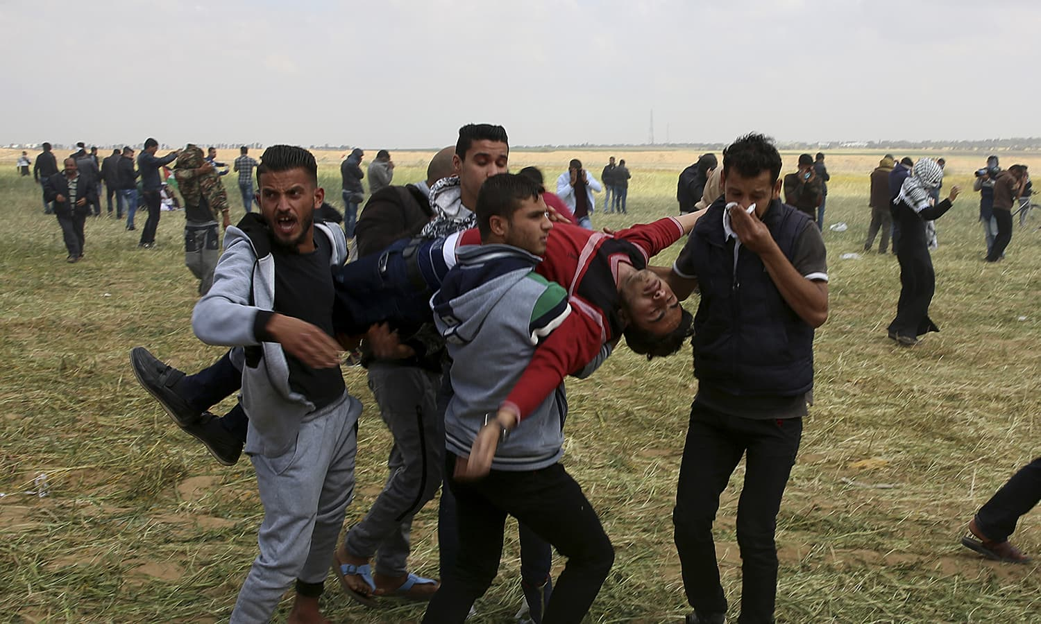 Palestinian protesters evacuate a wounded youth during clashes with Israeli troops along the Gaza Strip border. ─AP