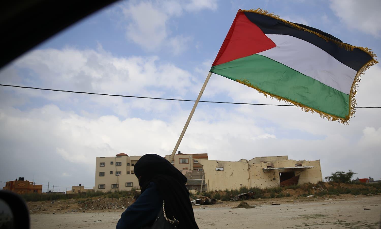 احتجاج میں خواتین بھی فلسطینی پرچم تھامے میدان میں موجود ہیں—فوٹو: اے ایف  پی