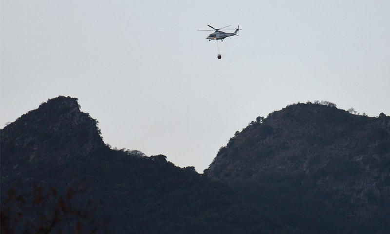 A helicopter, carrying a bucket filled with water, does sorties to extinguish the fire in the Margalla Hills on Friday. — Photo by Tanveer Shahzad