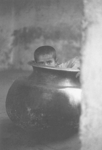 A boy sits in a cauldron at the Sakhi Sarwar shrine. Free food is doled out to the poor and pilgrims at shrines