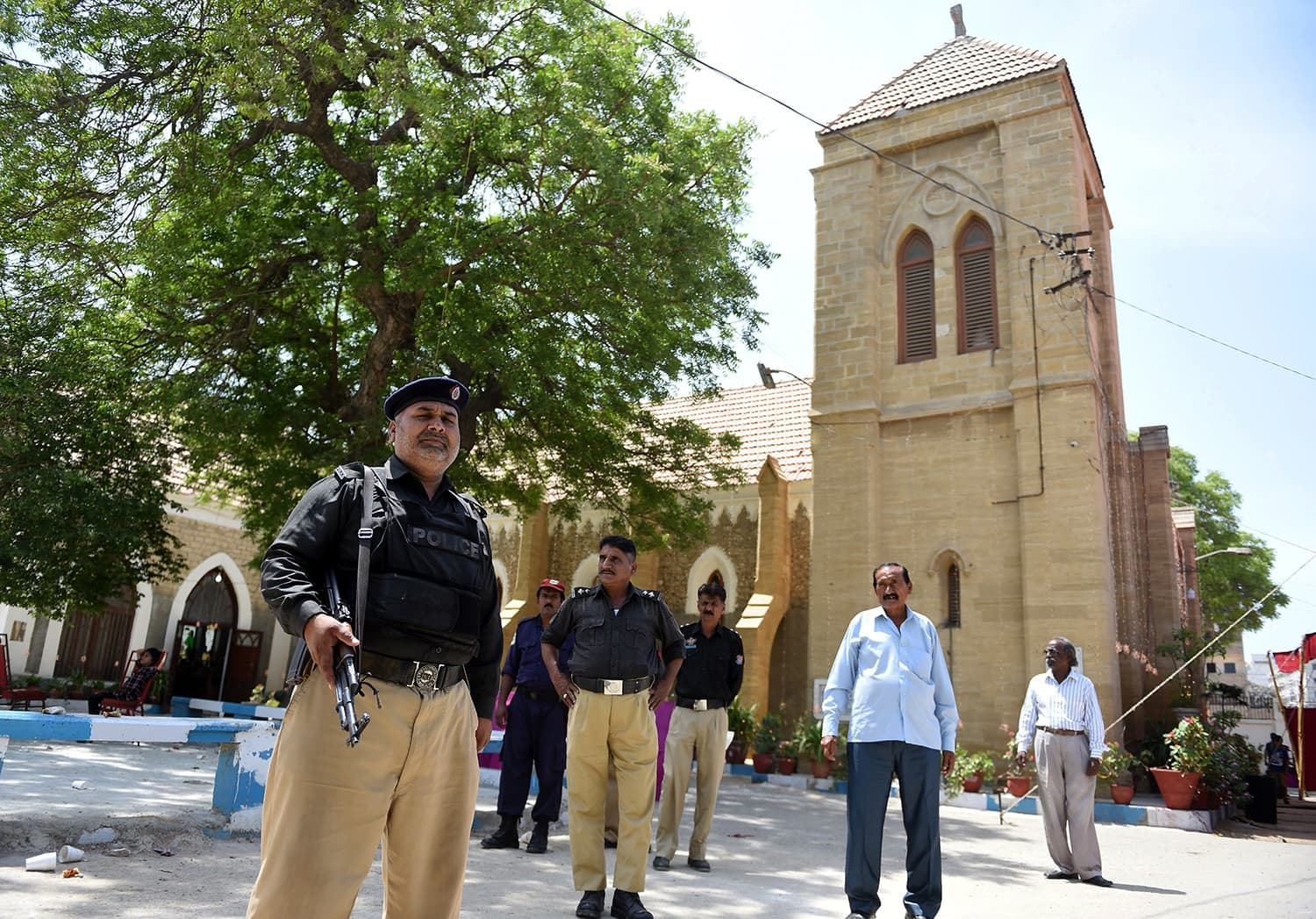 Policemen stand guard during the Easter mass at the Christ Church in Karachi. — AFP