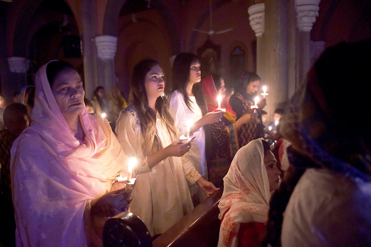Christian devotees holding candles while attending an Easter vigil mass at the Sacred Heart Church in Lahore. — AFP