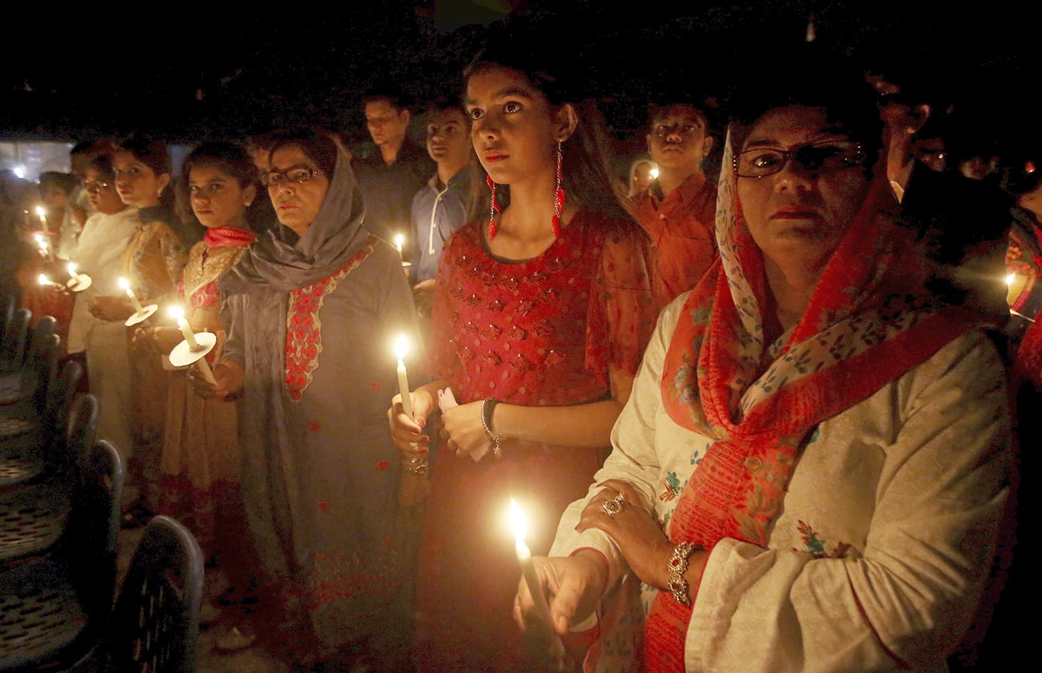 Christians hold candles while attending midnight Easter service at St Patrick church in Karachi. —AP