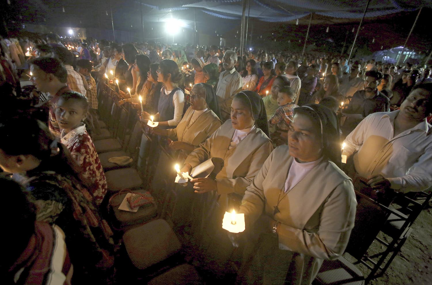 Christians hold candles while attending midnight Easter service at St. Patrick church in Karachi. —AP