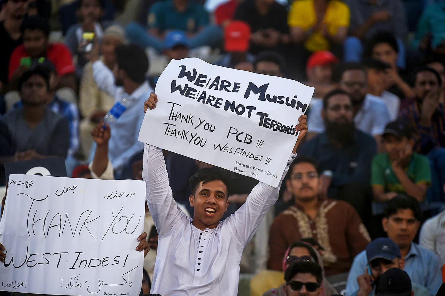 A cricket fan holds a placard as he watches the first T20 match between Pakistan and West Indies team. — AFP