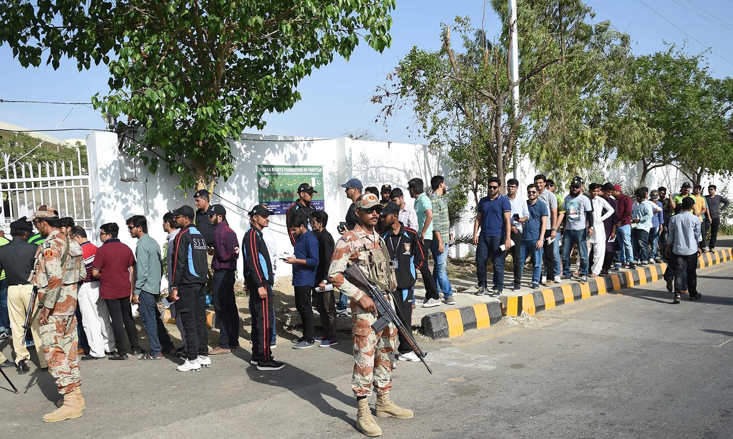 Rangers stand guard as cricket fans lineup at a security checkpoint outside the National Stadium before the first T20 match between Pakistan and West Indies. ─AFP