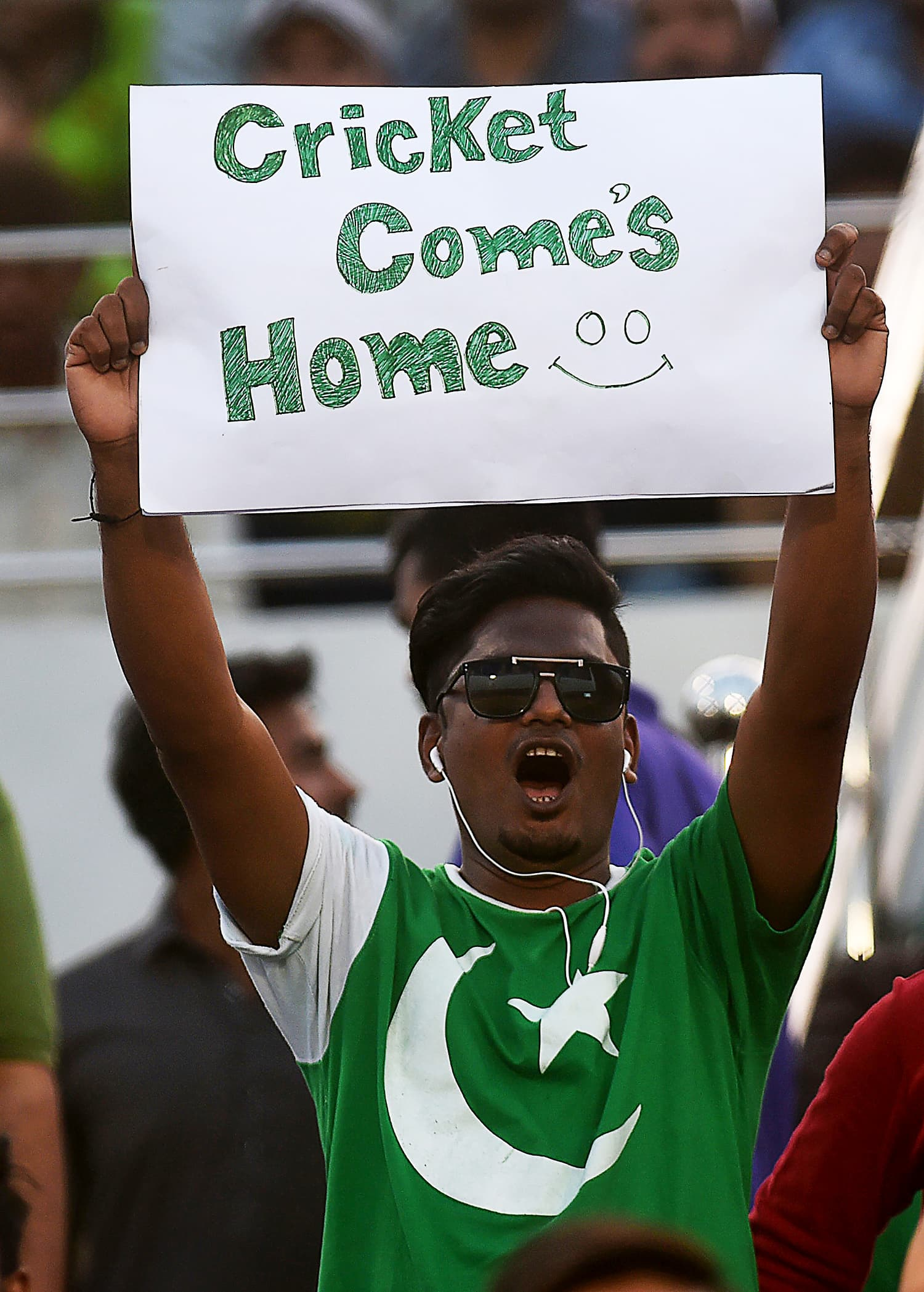A cricket fan holds a placard as he watches the first T20 match between Pakistan and West Indies team. ─AFP