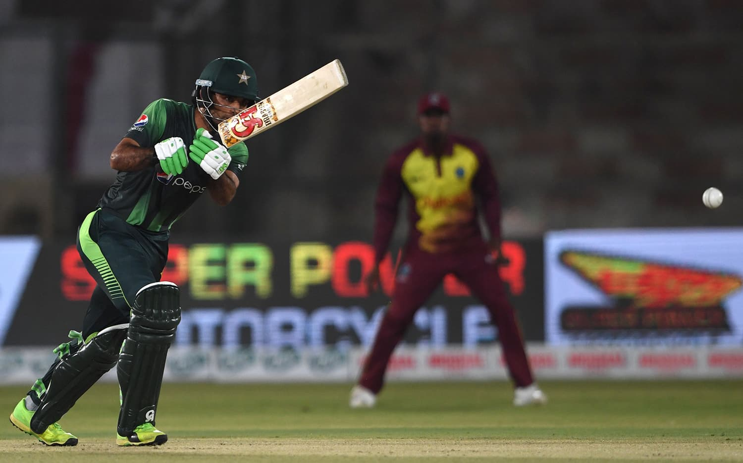 Fakhar Zaman watches the ball after playing a shot during the first T20 cricket match between Pakistan and West Indies. ─AFP
