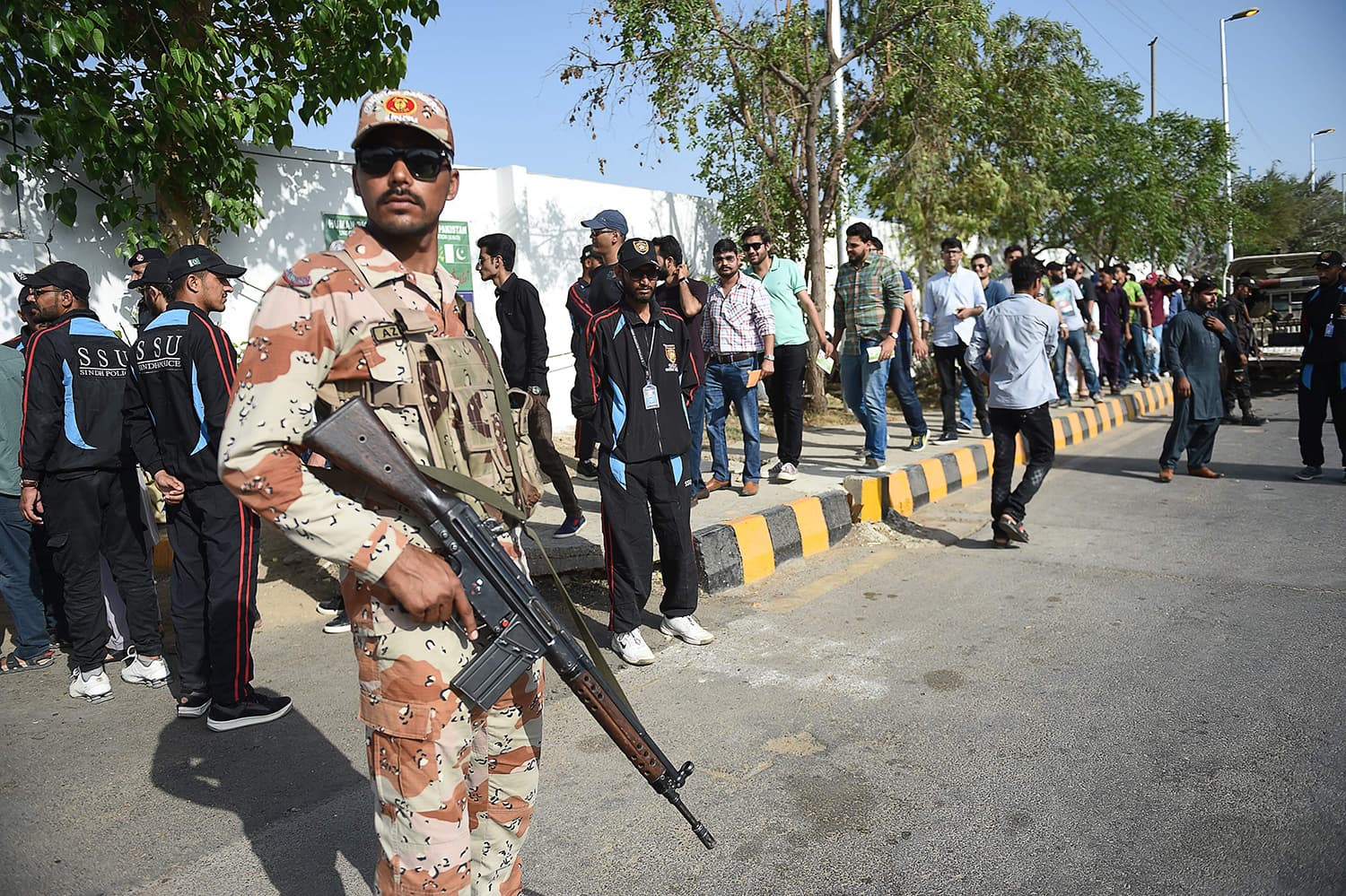A ranger stands guard as cricket fans lineup at a security checkpoint outside the National Stadium before the match. ─AFP