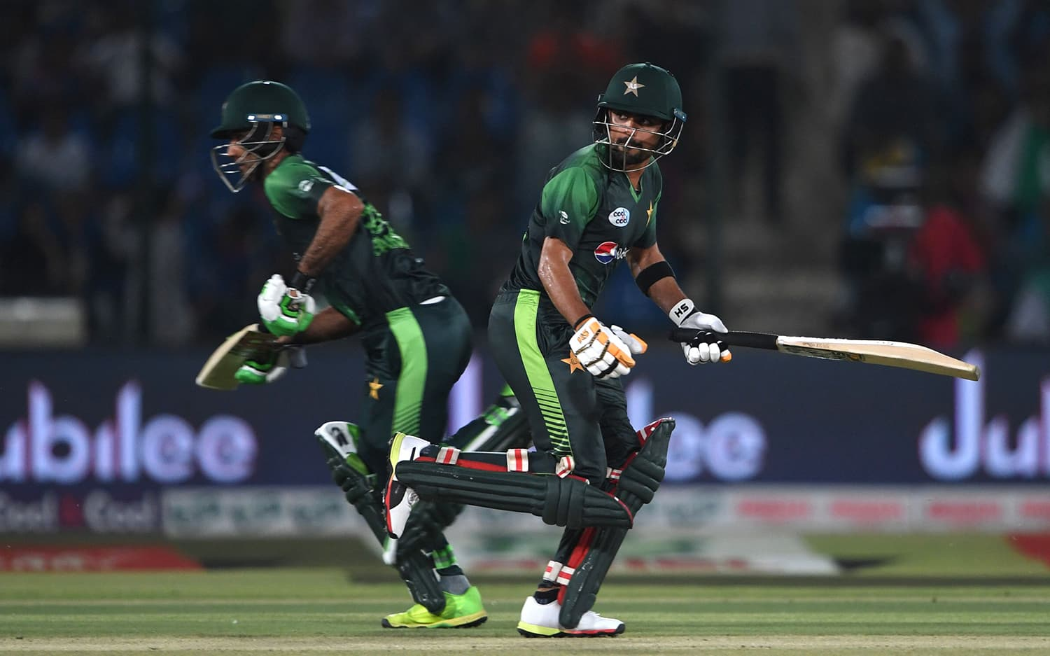 Fakhar Zaman and Babar Azam run between the wickets during the first T20 cricket match between Pakistan and West Indies. ─AFP