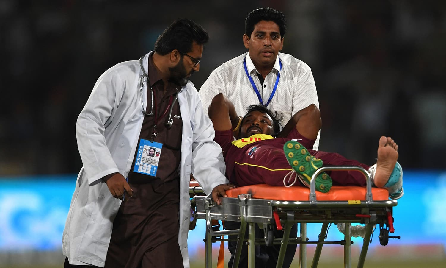 West Indies bowler Veerasammy Permaul gestures as he lies on a stretcher after injury during the first T20 cricket match between Pakistan and West Indies at The National Stadium in Karachi. ─AFP