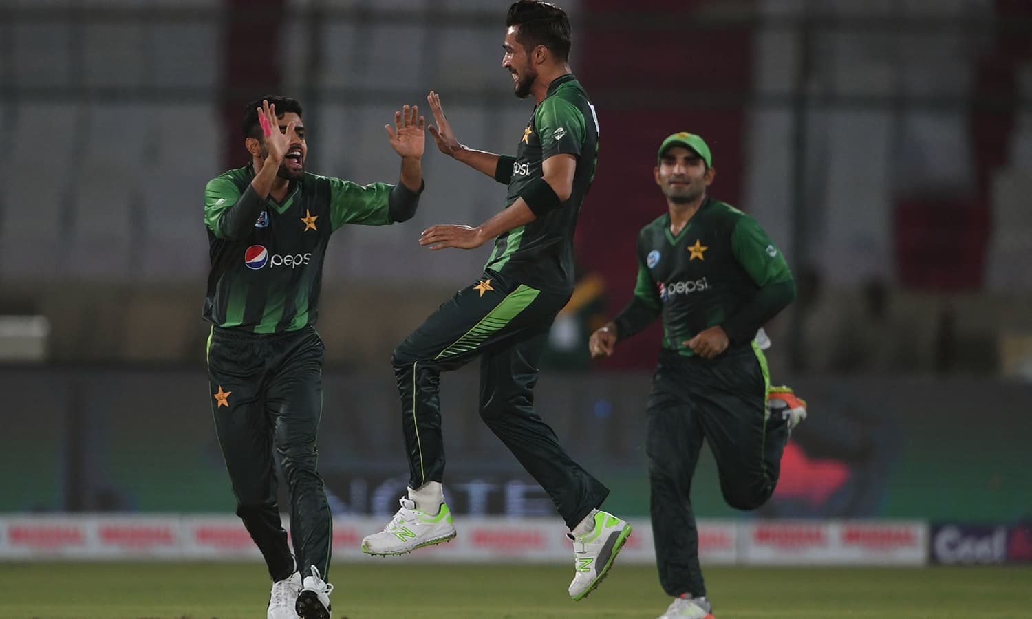 Mohammad Amir celebrates with teammates after taking the wickets of West Indies batsman Andre Fletcher. ─AFP