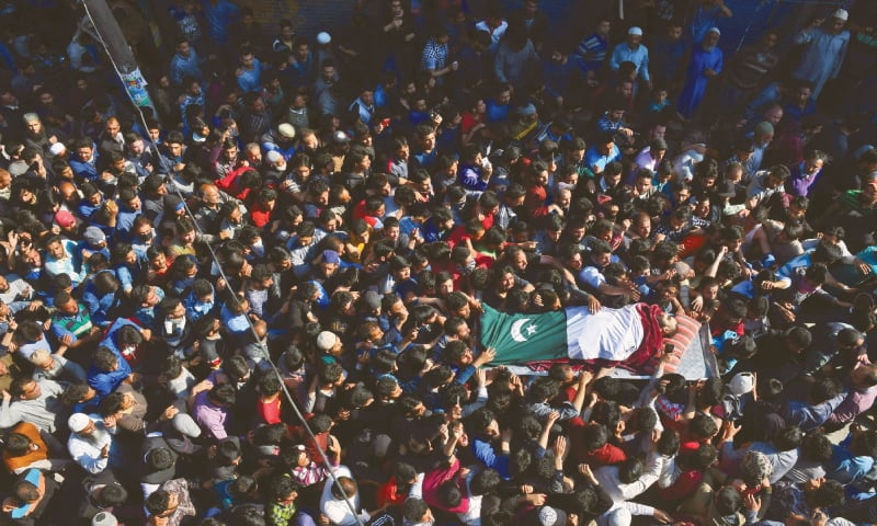 SHOPIAN: The body of a Kashmiri, wrapped in Pakistan flag, is being carried during his funeral on Sunday.—Reuters