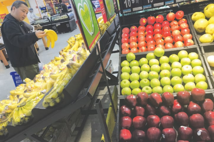 BEIJING: A man chooses bananas near imported apples from the United States at a supermarket on Monday.—AP