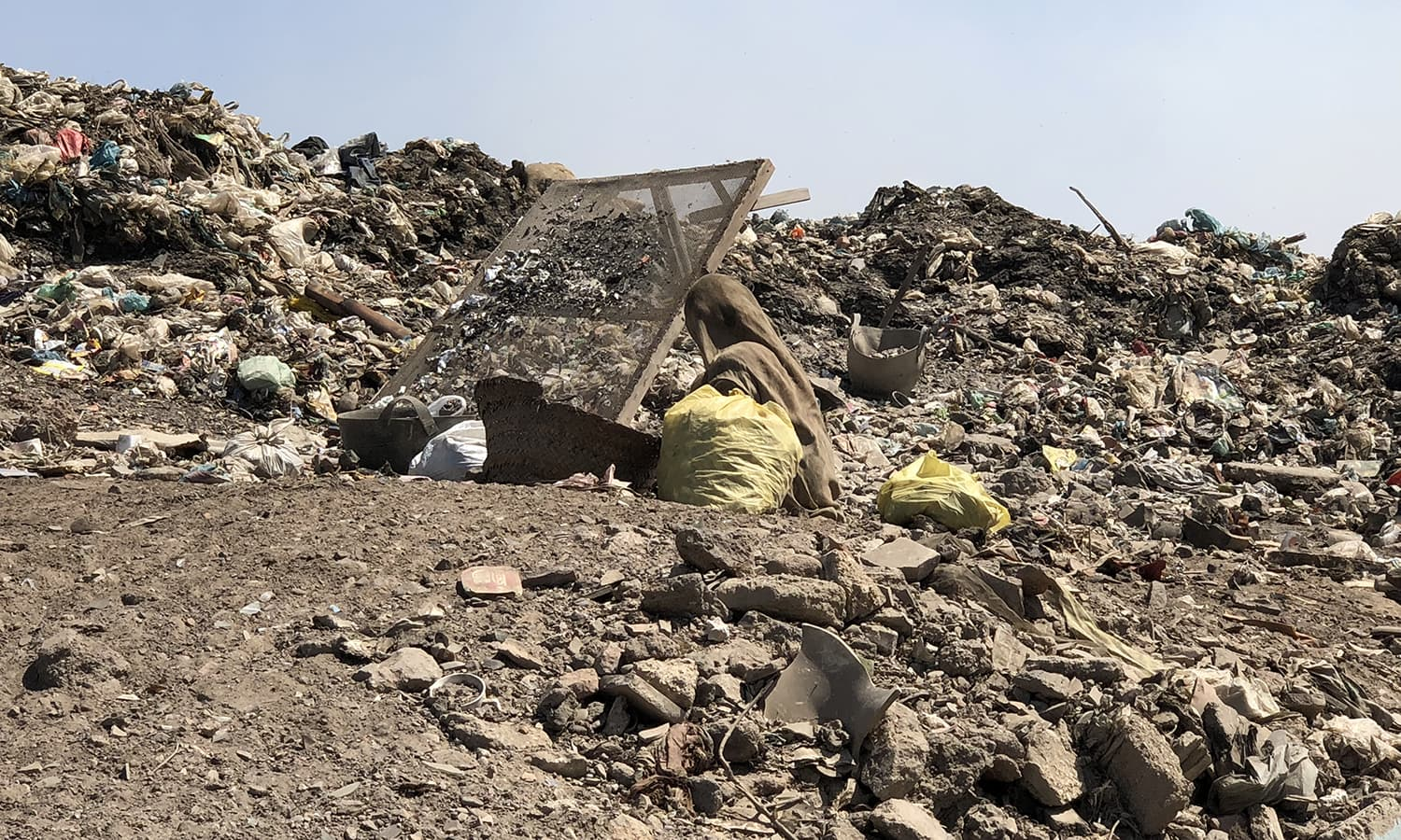 Razia Ghulam Hussain, a nymph of a woman, mother of five, busy sifting through garbage. — Photo by author
