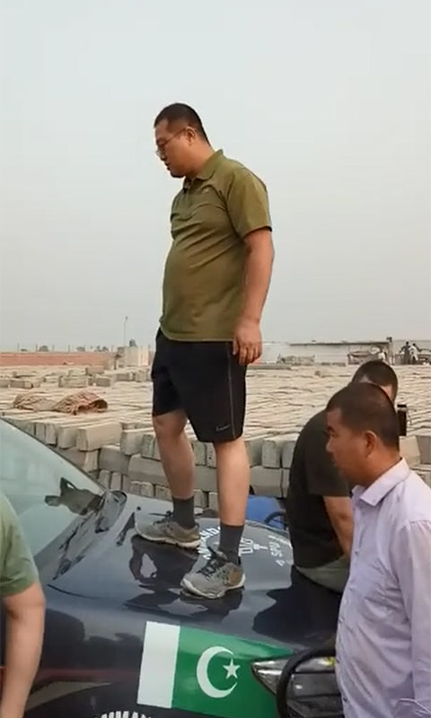 Screenshot shows a Chinese national standing on the bonnet of a police van.— DawnNewsTV