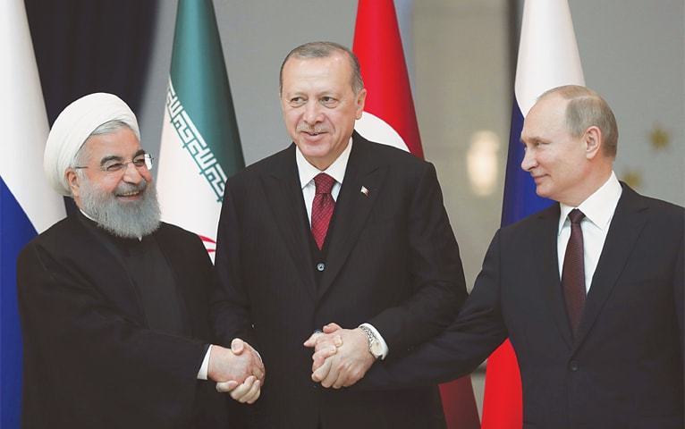 ANKARA: Iran's President Hassan Rouhani (left), Russia's President Vladimir Putin (right) and Turkey's President Recep Tayyip Erdogan lock hands symbolising unanimity of views on Wednesday. The three met in the Turkish capital for talks on Syria's future and reaffirmed their commitment to Syria's territorial integrity.—AP
