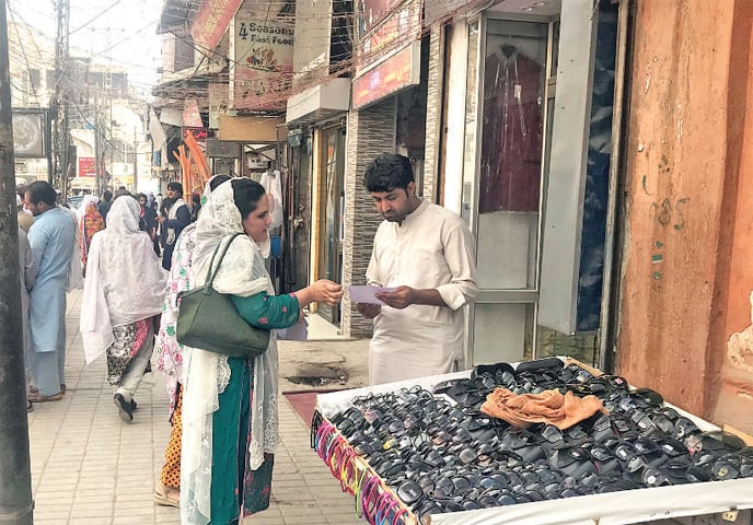 A Pakhtun Tahaffuz Movement activist distributes invitations to people in the busy Peshawar Saddar for the upcoming rally. — Dawn