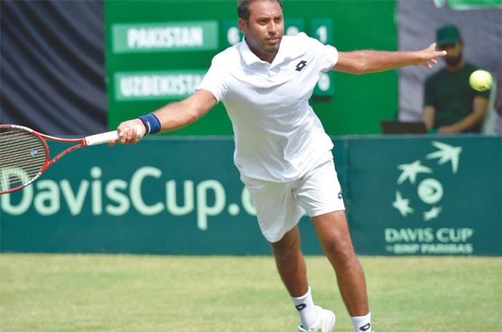 Veteran Aqeel Khan plays a forceful shot during his Davis Cup match.—White Star