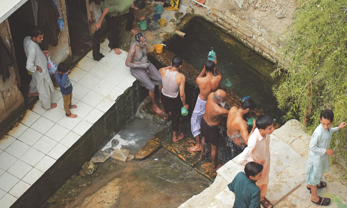 Men wash their bodies of ailments at a public bath below the shrine