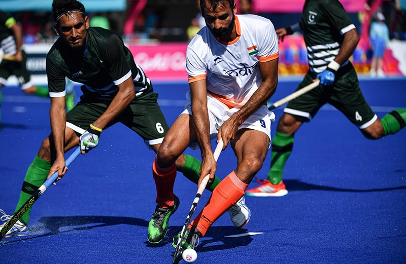 Gurjant Singh (C) of India controls the ball next to Tasawar Abbas (L) of Pakistan during their men's field hockey match. — AFP