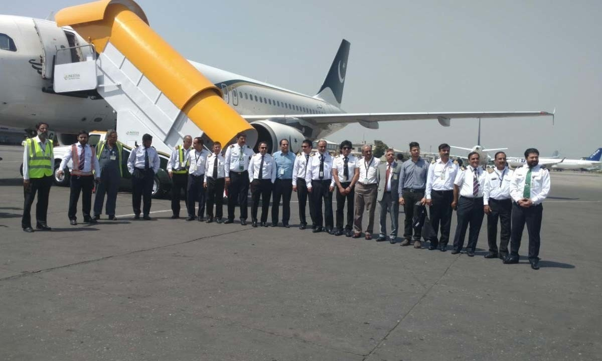 PIA's staff and crew outside the air plane set to carry them to the New Islamabad International Airport. — DawnNewsTV