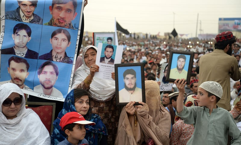PESHAWAR: Women hold pictures of their missing relatives during a demonstration on Sunday.—Shahbaz Butt / White Star