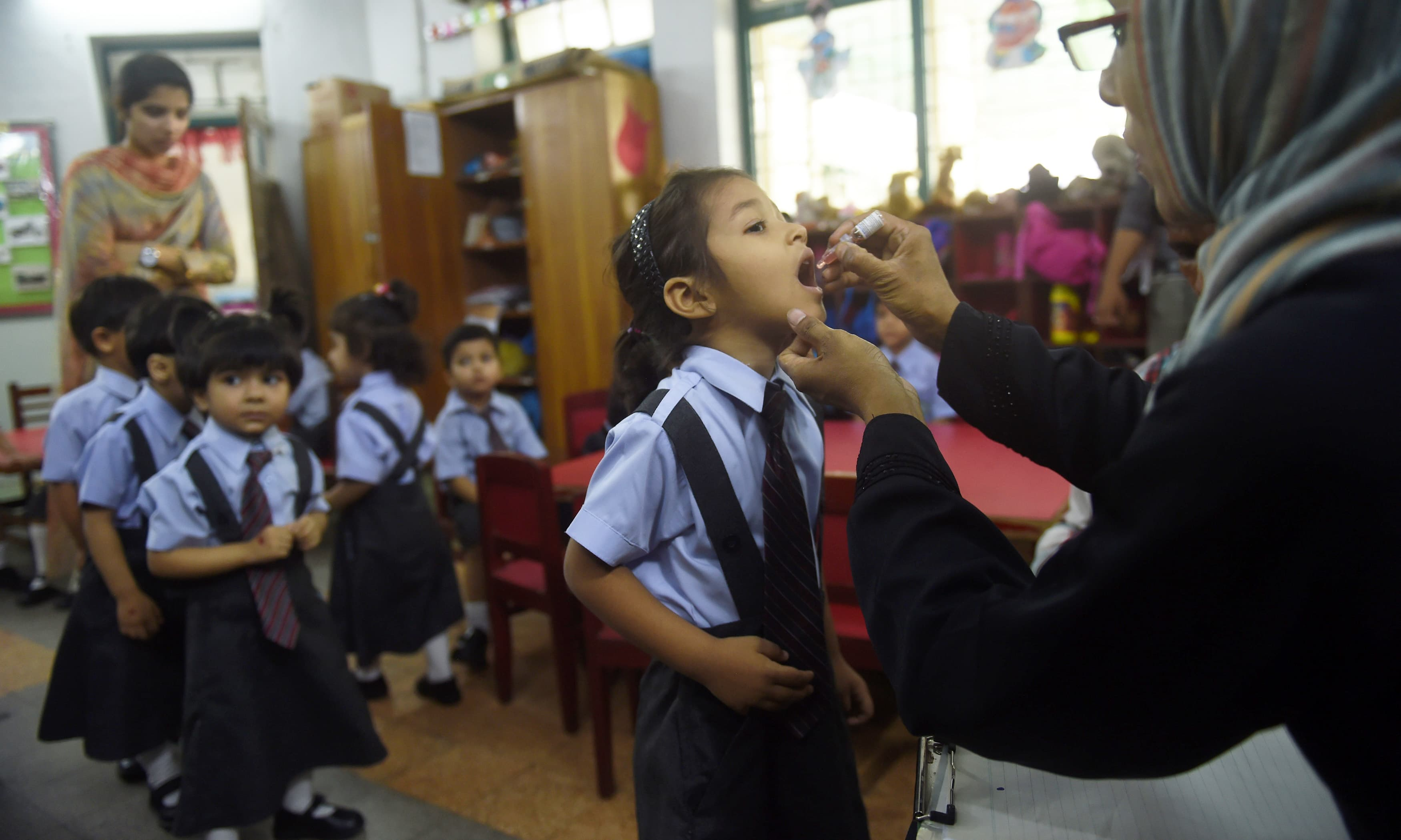 A health worker administers polio vaccine to a child at a school in Karachi. —AFP