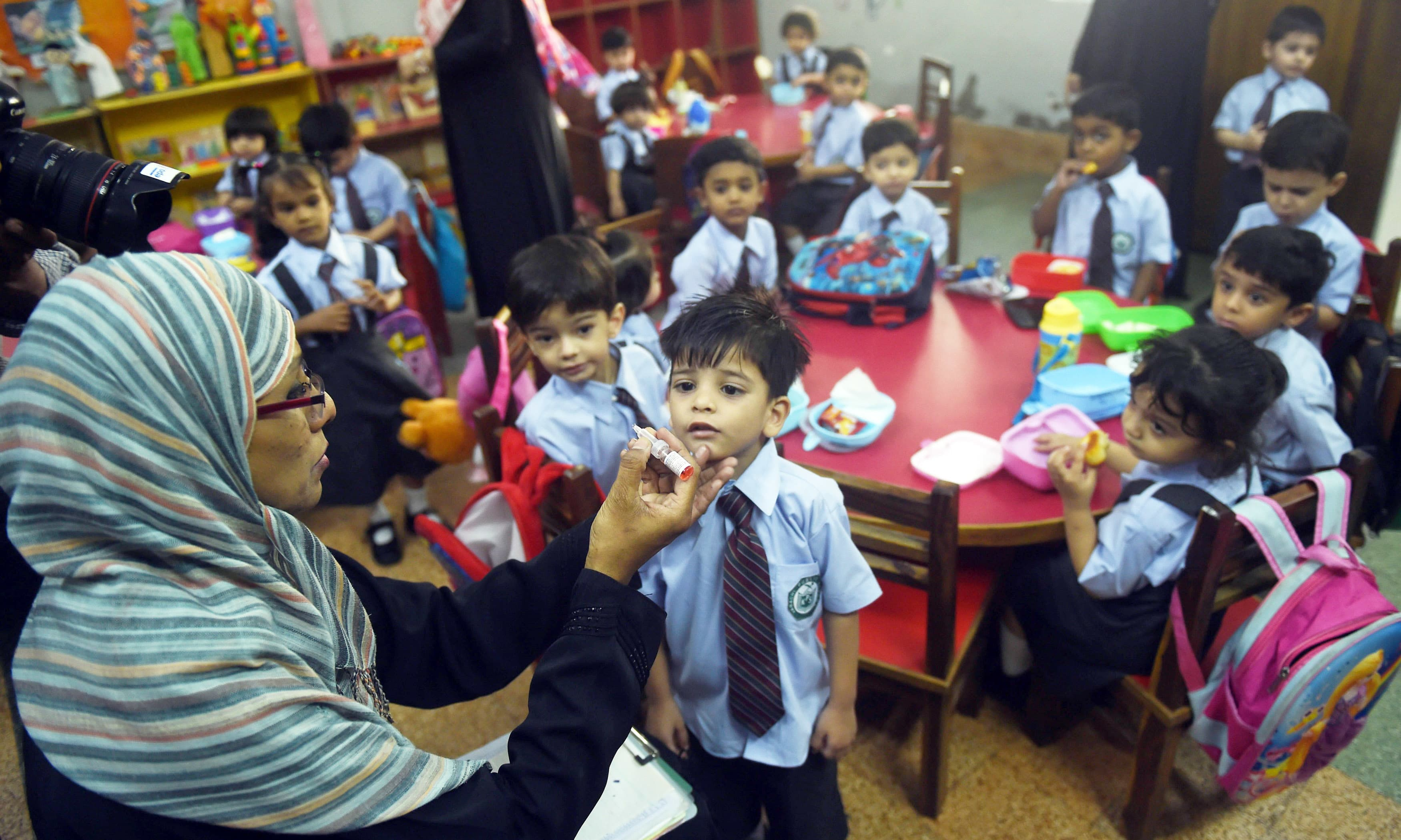 A health worker administers polio vaccine drops to a child at a school during a polio vaccination campaign in Karachi. —AFP