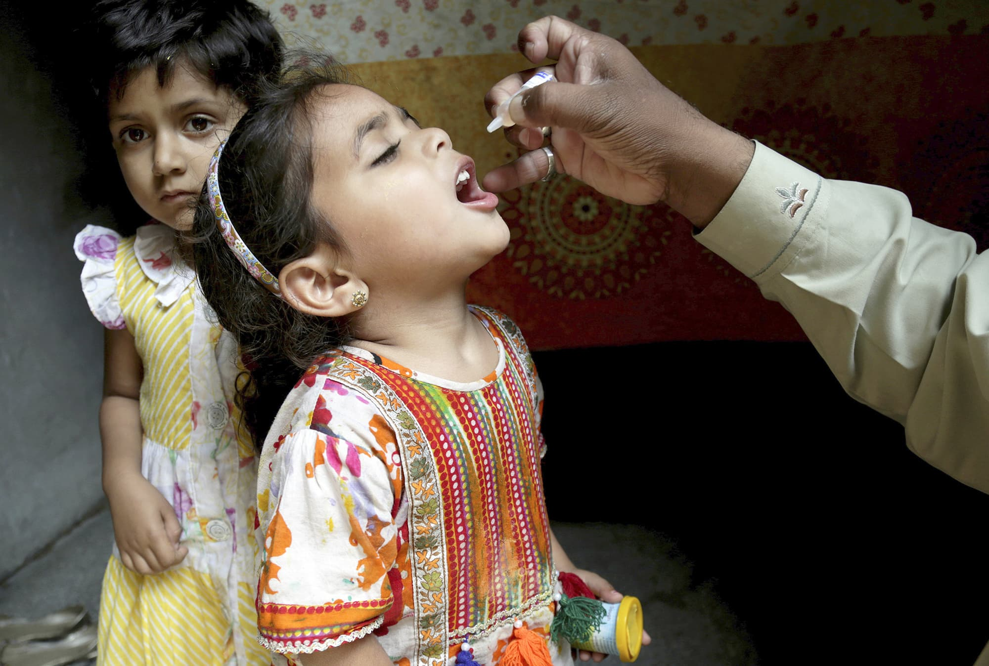 A health worker gives a polio vaccine to a girl in Lahore, Pakistan, Monday, April 9, 2018. A Pakistani official said authorities launched a new polio vaccination drive, aiming to reach 38.7 million children under the age of 5. (AP Photo/K.M. Chaudary) — Copyright 2018 The Associated Press. All rights reserved.