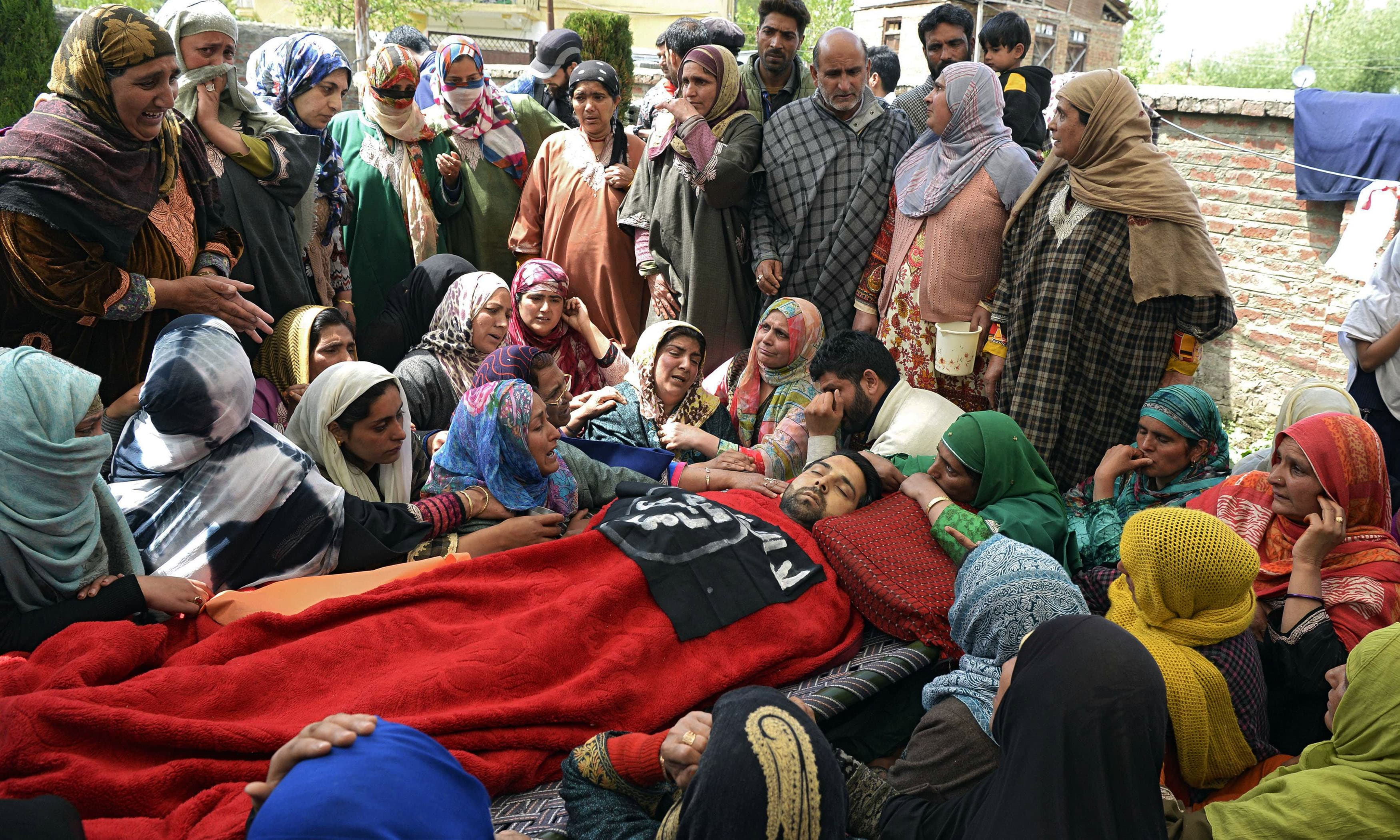 Villagers mourn near the body of slain Kashmiri youth Sharjeel Ahmed. —AFP