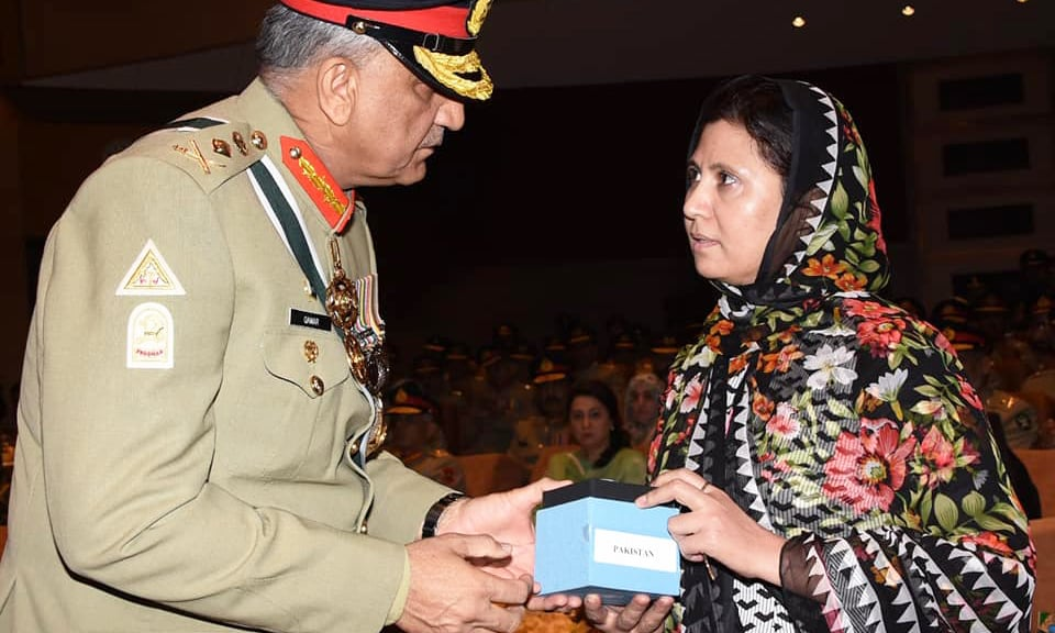 Gen Bajwa presenting an award to the heir of a martyred personnel. ─ISPR