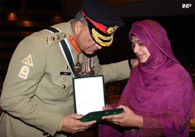 RAWALPINDI: Chief of the Army Staff Gen Qamar Javed Bajwa gives a medal to a woman whose relative embraced martyrdom in the line of duty during a ceremony held at the General Headquarters on Thursday.—INP