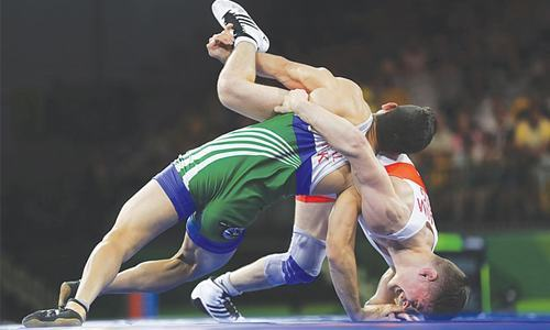 GOLD COAST: Pakistan's Muhammad Bilal (L) wrestles with England's George Ramm to win Bronze medal in men's freestyle 57Kg wrestling at the Commonwealth Games on Thursday.—AP