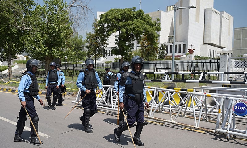 Riot policemen patrol outside the Supreme Court building during a protest by supporters of the ruling PML-N.