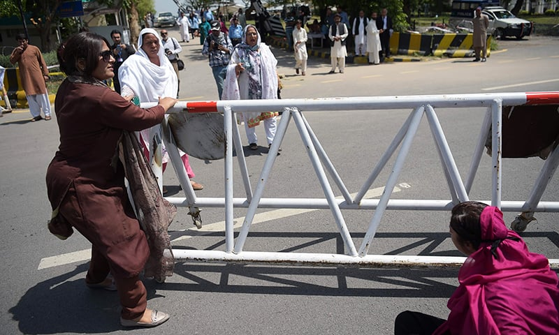 Supporters of the ruling PML-N block a street beside the Supreme Court building during a protest against the court's verdict. — AFP